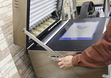 追い焼き(空焼き)の工程。現像後の版をセットし、紫外線を照射させ、イメージ部分の感光膜を完全に硬化させる。
