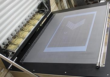 紫外線露光の焼き付け機。シートの下から空気が抜かれ、亜鉛版とネガフィルムとがぴったり密着する。