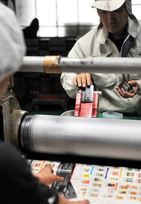 (写真3)エンボス機に一枚ずつ手差しで入れていく。