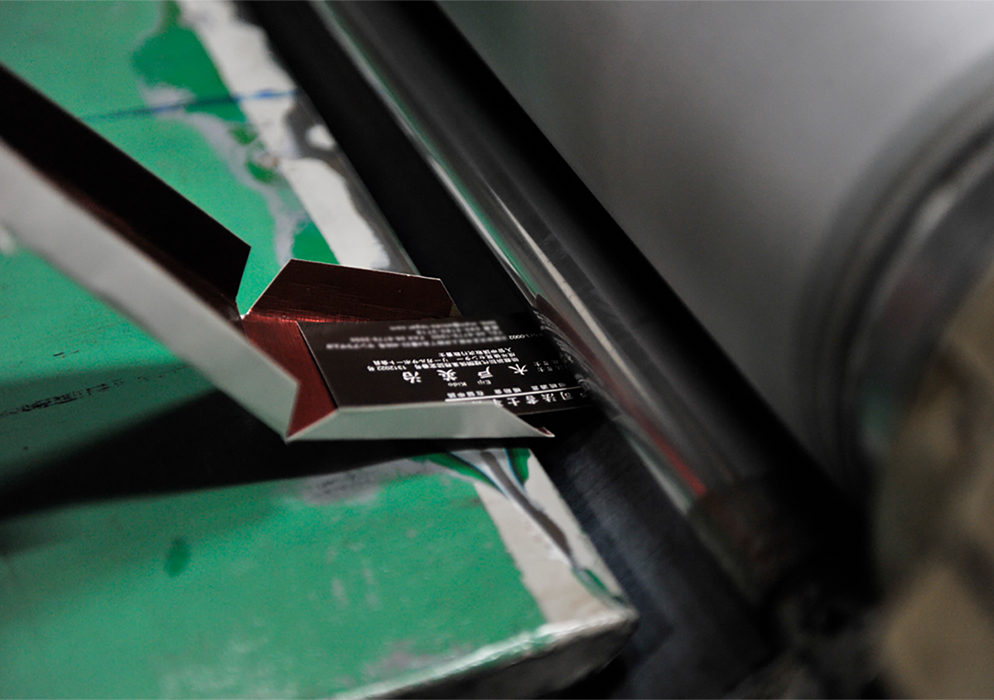 (写真4)エンボス機に一枚ずつ手差しで入れていく。