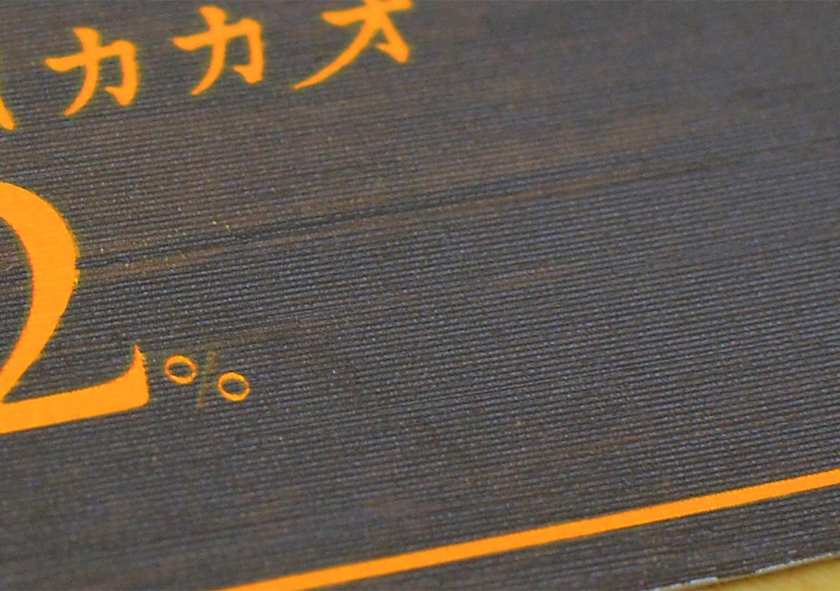 (写真1)チョコレート菓子のパッケージ。木目調の印刷に、線柄のエンボスが浅く施されている。 | 第6回「デザインエッセンスとしてのエンボス加工」 - 池ヶ谷紙工所 | 活版印刷研究所