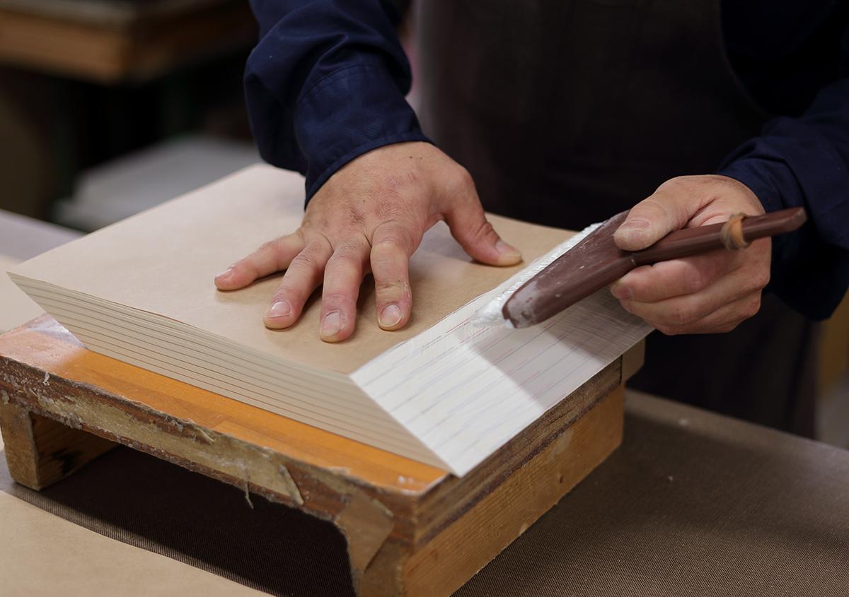 (写真20)背を糊で固める(「ザク固め」というそうで、ほんの強度を出しています)。 | 『くままでのおさらい 特装版』が「 世界で最も美しい本コンクール 」銀賞を受賞 - 生田信一(ファー・インク) | 活版印刷研究所