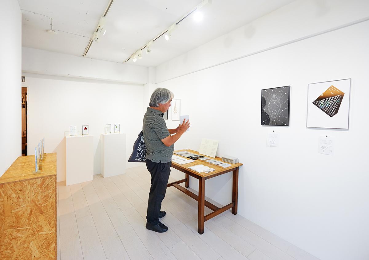 (写真2)「植物標本と活版印刷」展の風景。落ち着いた空間の中で、じっくり作品に触れることができました。写っている人物は筆者。:撮影スズキアサコ | 個展「 植物標本と活版印刷 」を訪ねる - 生田信一(ファーインク) | 活版印刷研究所