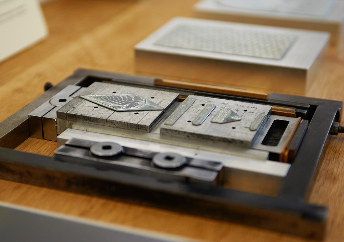 (写真12)印刷版の展示。亜鉛版は直方体の金属のブロックに固定され、印刷機にセットされるしくみ。繊細な図案が金属の凹凸で再現されているのがわかる。 | 個展「 植物標本と活版印刷 」を訪ねる - 生田信一(ファーインク) | 活版印刷研究所