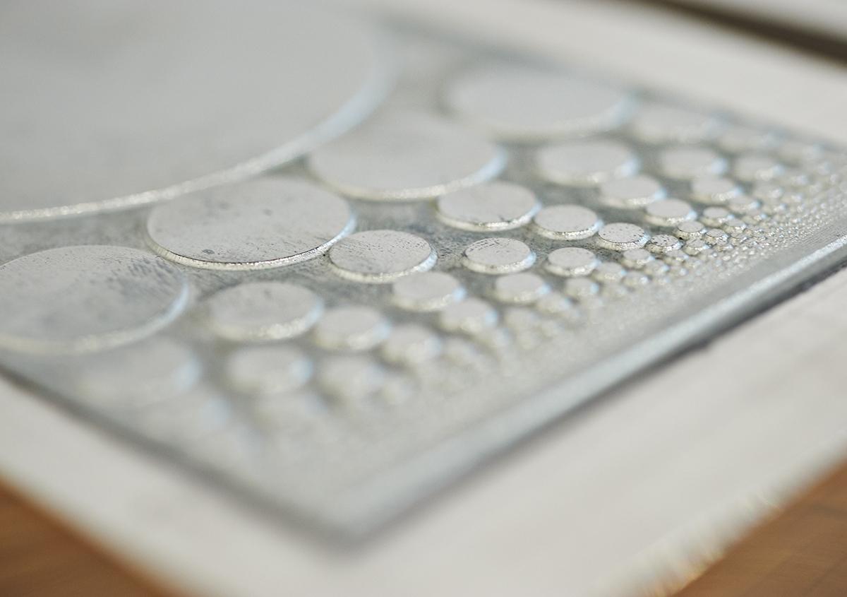 (写真15)印刷版の展示。亜鉛版は直方体の金属のブロックに固定され、印刷機にセットされるしくみ。繊細な図案が金属の凹凸で再現されているのがわかる。 | 個展「 植物標本と活版印刷 」を訪ねる - 生田信一(ファーインク) | 活版印刷研究所