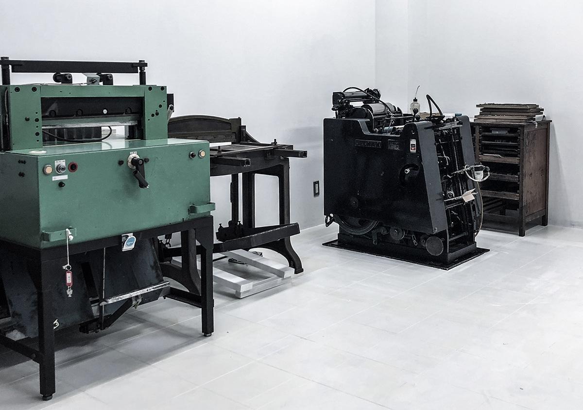 (写真1)手動、半手動、自動の印刷機器が並ぶ仕事場。名刺サイズからB4サイズのポスターが印刷できる環境が整っている。 | 活版印刷の技術で、複製できない価値を生み出す - 生田信一(ファーインク) | 活版印刷研究所