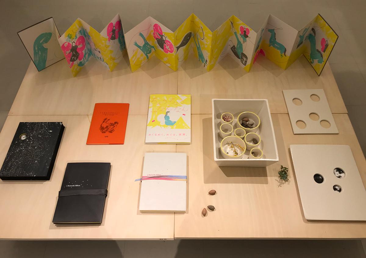 (写真9)上はジャバラの本を展開したもの。左は、本を収納する黒の夫婦箱のブックケース。右は本を収める陶製の箱。 | 絵本『ちょうちょうなんなん』から派生した『a Butterfly Effect』展 - TOPICS | 活版印刷研究所