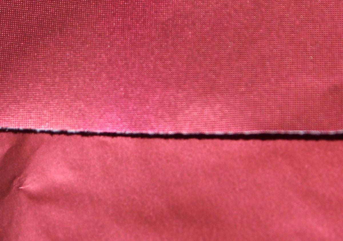 (写真10)メタリック色の赤い用紙にエンボス加工を加えている。上が加工後、下が加工前。 | 紙に質感や模様を与えるプレス加工──池ヶ谷紙工所さんの話を聞きました - 生田信一(ファーインク) | 活版印刷研究所
