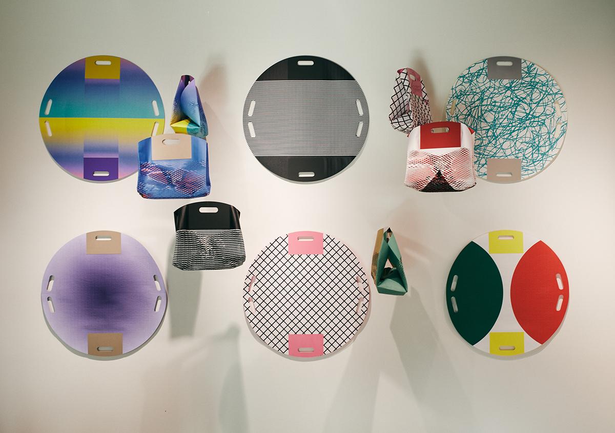 (写真10)「紙の包み袋」の展示。円形の紙を組み立てるとバッグになります。用紙はシャルク(並口)、ファンタス(四六判 270kg)、OK ACカード(#400)、ディープマット(四六判 450kg)、ケンラン(四六判 400kg)、キュリアススキン(700×1000mm 189kg)を使用。 | 平和紙業 ペーパーボイス東京がリニューアル、「PPP」展に行ってきました - 生田信一(ファーインク) | 活版印刷研究所