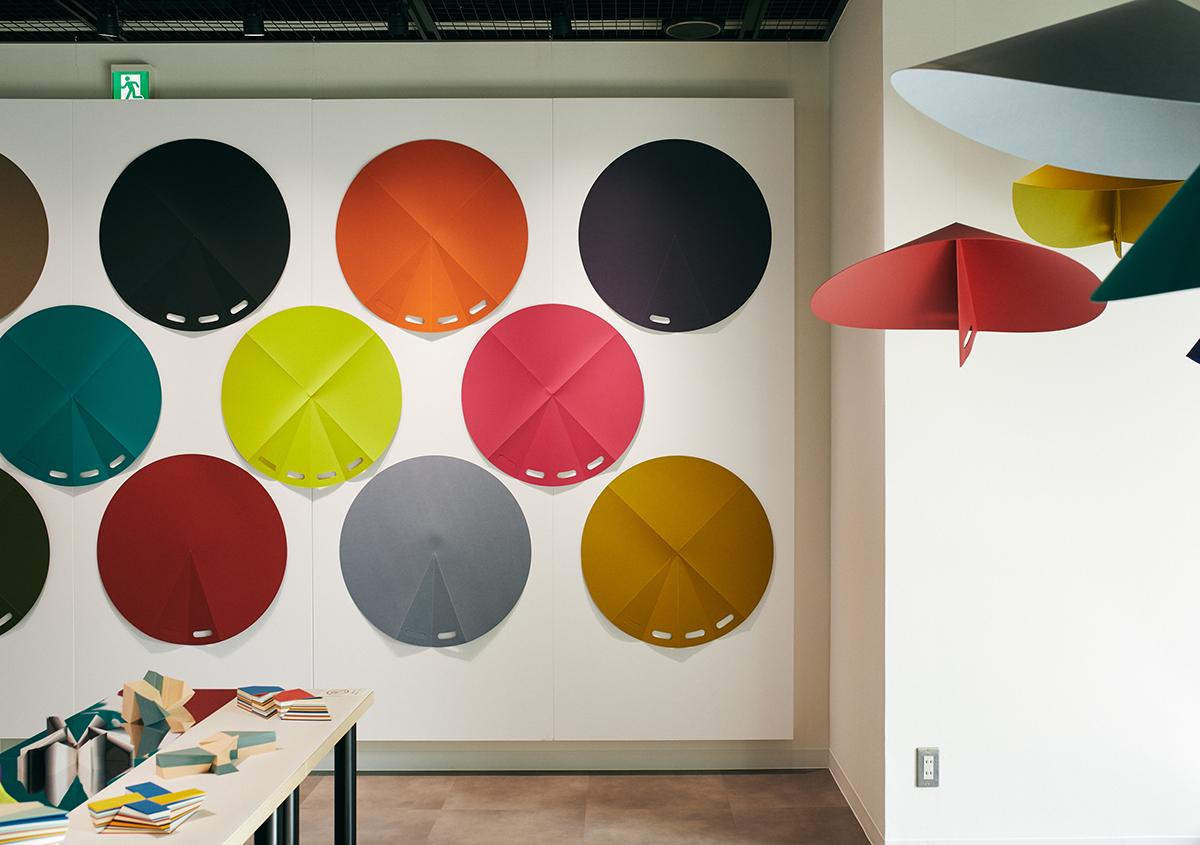 (写真12)「紙の日よけ/雨よけ」の展示。円形の紙を折ると、日よけ/雨よけの傘になります。ディープマット(四六判 450kg)、キュリアススキン(700×1000mm 189kg)を使用。 | 平和紙業 ペーパーボイス東京がリニューアル、「PPP」展に行ってきました - 生田信一(ファーインク) | 活版印刷研究所