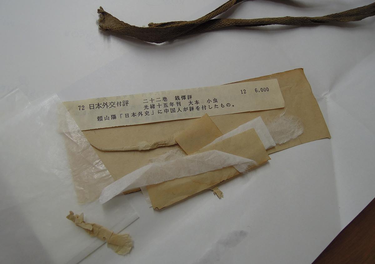 (写真8)挟みものやこより、元の修理に使用されていた紙など   ある漢籍の修理 - 京都大学図書館資料保存ワークショップ   活版印刷研究所